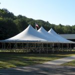 30x60 Pole Tent set with tables and chairs for a corporate event with american flag in the background.