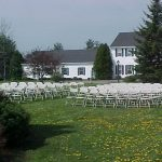 Samsonite Folding Chairs setup for a Wedding Ceremony in front of garden