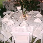 Simple setting with white party chairs and white stripe tablecloths