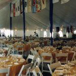 Large pole tent with decorated center poles, Full table settings with linens and white party chairs